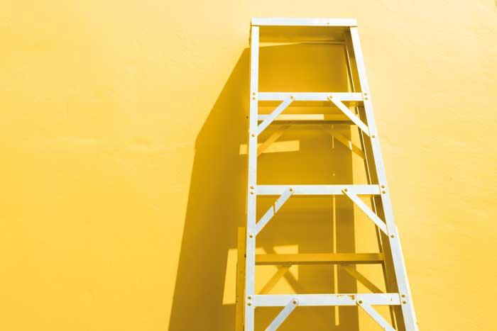 Step Ladder propped up against yellow wall